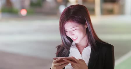 başarılı : woman play mobile game in city at night Stok Video