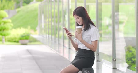 mulheres : businesswoman take coffee and use phone happily Stock Footage