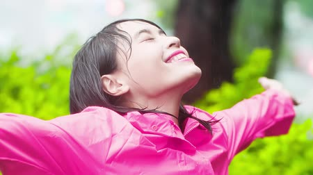 raincoat : woman wear raincoat and enjoying the rain