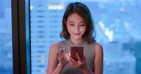 sorridente : woman use phone happily in building at night