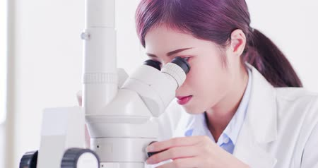 биохимия : woman scientist use microscope in the laboratory