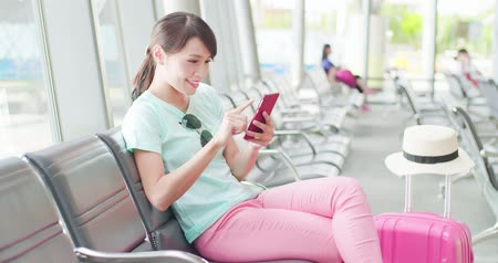 bavul : woman sit and use phone happily in the station