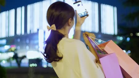 travel footage : woman take shopping bag and selfie happily at night