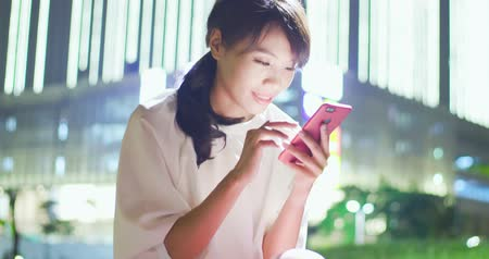 послать : woman text message and use phone happily in the evening Стоковые видеозаписи