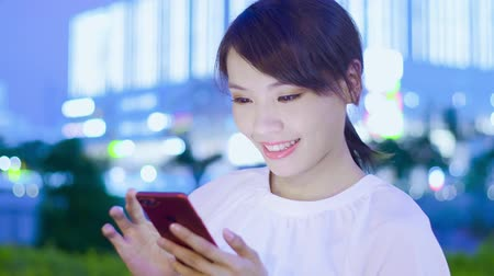 gotículas : woman use smart phone happily at night Stock Footage