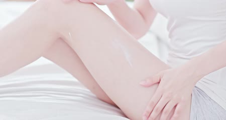 cuidados com o corpo : Woman sitting on bed and applying cream onto her leg Vídeos