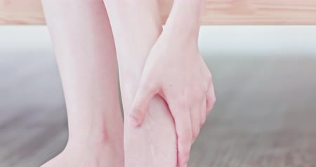 sağlıklı yaşam : Woman sitting on bed and applying cream onto her foot at home Stok Video