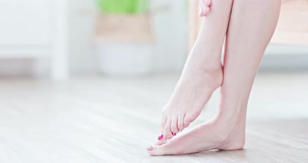 toes : Woman sitting on bed and applying cream onto her foot at home Stock Footage