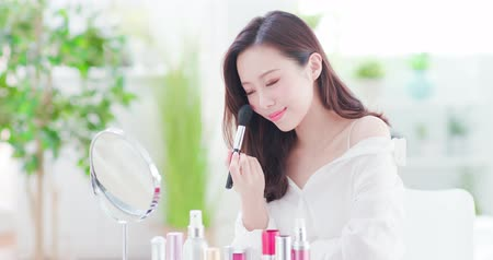 тени для век : Smile woman with makeup brushes near face and look mirror at home Стоковые видеозаписи