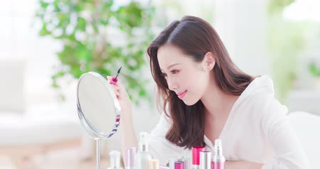 rímel : Beautiful Woman using mascara brush and look mirror at home Vídeos