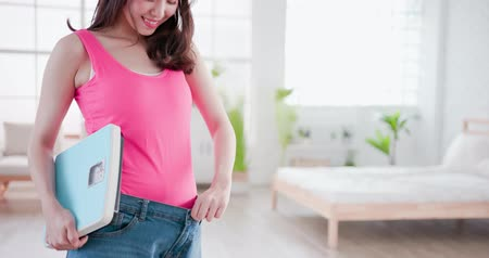 female measurements : beauty woman show loose jeans with weight scale