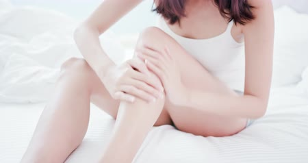 sunblock : Woman applying cream onto her leg and shin at home