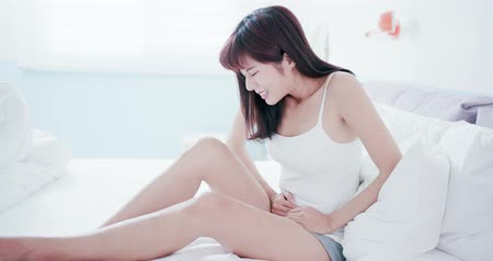 painéis : woamn feel pain with menstruation on the bed at home