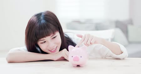 prase : Happy woman look her pink piggy bank and feel happy at home