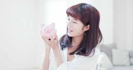 emekli olmak : Happy woman save money to her pink piggy bank and kiss it at home
