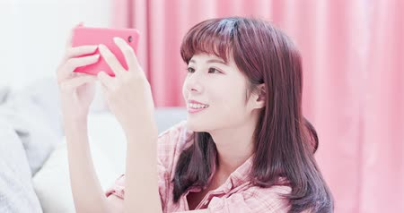 kanapa : woman play mobile game by smart phone happily and sit on the sofa at home