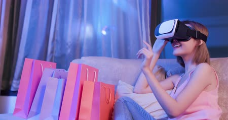 película de filme : woman shopping online with VR headset on sofa colorful shopping bags around Stock Footage