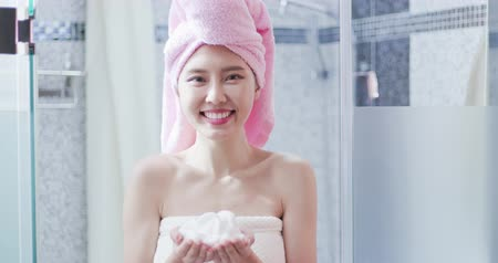 увлажняющий : woman with facial Cleansing foam in the bathroom after shower