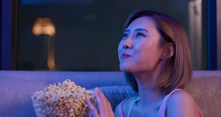 watch tv : Young woman cry while watching a very moving movie with popcorn at night