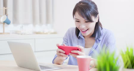 phone entertainment : woman play mobile game by smart phone happily at home