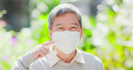 носить : old man smile show thumb up and wear mask with nature green background