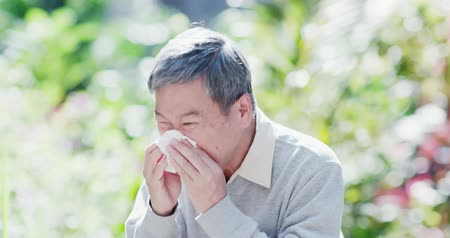 zsebkendő : old man sick and sneeze with tissue paper outdoor