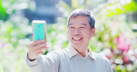 privacy : old man use smart phone unlocking with biometric facial identification outdoor