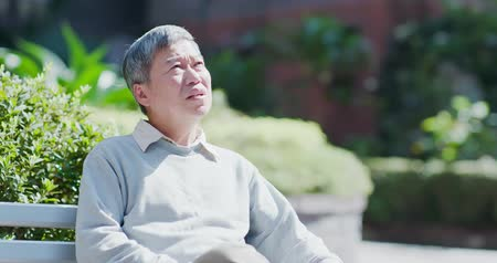 errado : old man depressed and forget something outdoor Stock Footage
