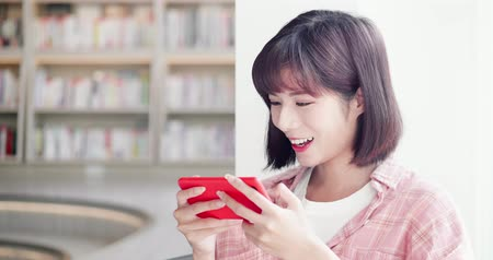 könyvesbolt : young woman play mobile game and use smart phone in the library Stock mozgókép
