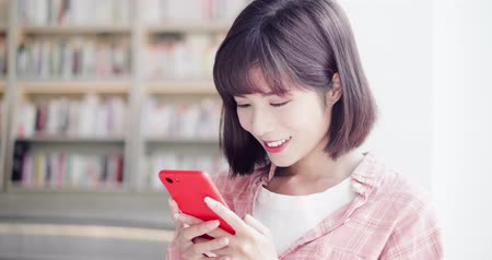 biblioteca : young woman send message by smart phone indoor