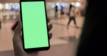 lányok : business woman take phone with green screen in airport at sinpapore Stock mozgókép