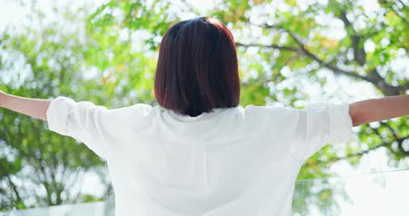 trecho : Back view of young woman feel carefree and take a deep breath at nature outdoor