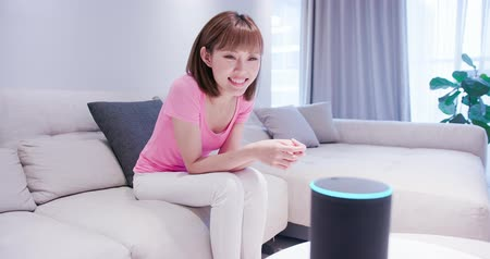 vokální : Smart AI speaker concept - Young Woman talk to voice assistant at home and feel happy