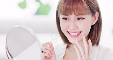 removable : Beauty woman look her beautiful teeth in the mirror happily after take off the brace retainer for tooth Stock Footage