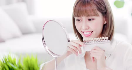 srovnávat : Beauty woman look her beautiful teeth in the mirror and check the color of the teeth Dostupné videozáznamy