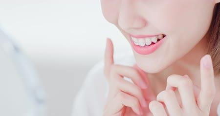 口腔病学 : Close up of Beauty woman wear retainer for teeth and look mirror happily