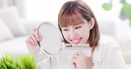 fogászat : Beauty woman look her beautiful teeth in the mirror and check the color of the teeth Stock mozgókép