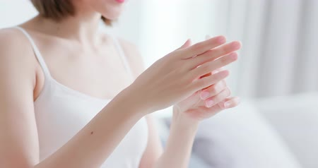essência : beautiful woman dropping collagen moisturizer into her hand at home