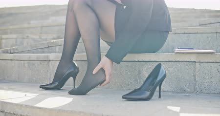cramps : slow motion of business woman with leg cramps and ankles pain from high heels.