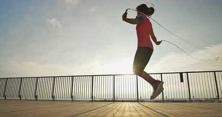iluminado para trás : Silhouette slow motion of woman sport and rope skipping with sunset Stock Footage