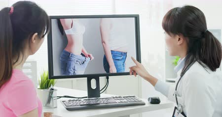 esvoaçantes : Plastic surgeon doctor explain liposuction to a patient with computer monitor in the clinic