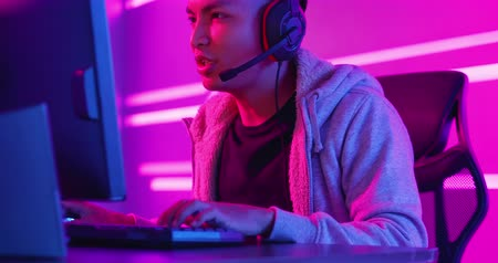 auscultadores : Profile of Young Asian Handsome Pro Gamer Playing in Online Video Game Stock Footage