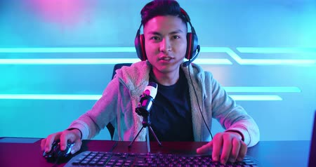 söylemek : Young Asian Handsome vlogger having live stream and playing in Online Video Game