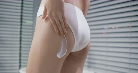 pleťová voda : slow motion of Beauty woman applying cream or lotion onto her legs and buttocks in the bathroom at night