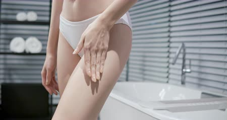 coxa : slow motion of Beauty woman applying cream or lotion onto her leg in the bathroom at night