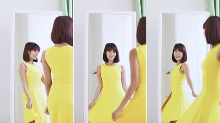 tentar : set of vertical video - slow motion of asian girl trying dress and take a selfie in mirror happily