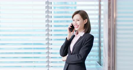 estagiário : Young asian business woman speak smart phone in the office