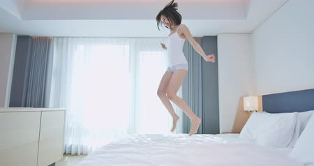 bare foot : Young happy woman feel carefree and jump on bed at home Stock Footage