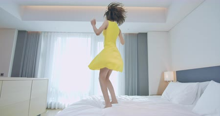 postel : Fashion young lady feel carefree and jump on the bed in a hotel room while traveling Dostupné videozáznamy