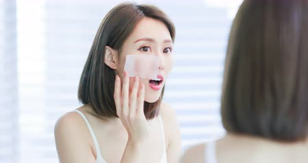 weefsel : Young asian skin care woman upset after use oil blotting paper on her face